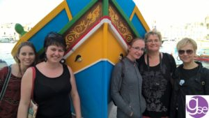 Gateway School of English students with a Maltese fishing boat in Marsaxlokk Bay